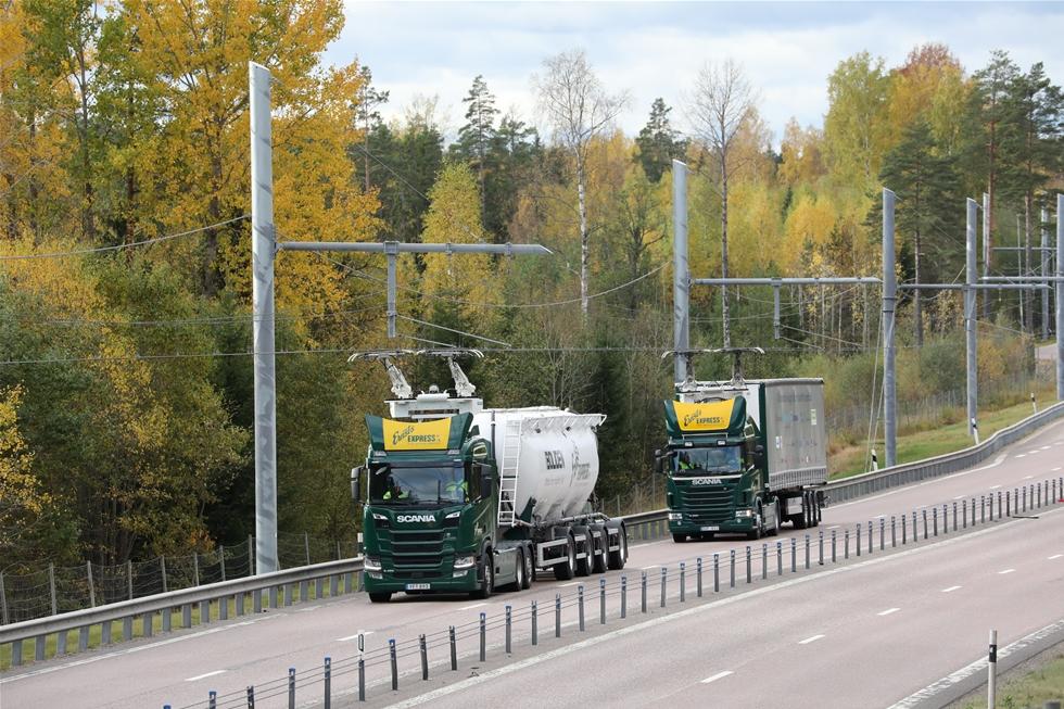 Två bilar kör teststräckan utanför Sandviken. Stolpar med 60 meters mellanrum bär två elledningar. I rätt ögonblick fälls en strömavtagare upp från lastbilens tak och laddar elmotorn. Vid inbromsningar går energi tillbaka till systemet. Annars drivs bilen av en dieselmotor av fossilfri syntetisk diesel. Foto: Jan Nylander.